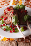 Beef steak with pomegranate seeds and basil close-up. Vertical Royalty Free Stock Photo