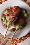 Beef steak with pomegranate seeds and basil close-up. vertical t Royalty Free Stock Image
