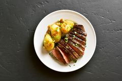 Beef steak with potato and caramelized onion. In plate on black stone background. Top view, flat lay stock images
