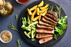 Beef steak with potato wedges and cucumber salad. Close up of steak medium rare beef with potato wedges and cucumber salad on wooden board over stone background stock images