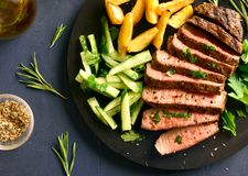 Beef steak with potato wedges and cucumber salad. Close up of steak medium rare beef with potato wedges and cucumber salad on black wooden board over stone table stock photography