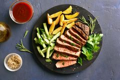 Beef steak with potato wedges and cucumber salad. Steak medium rare beef with potato wedges and cucumber salad on wooden board over black stone background. Top stock photos