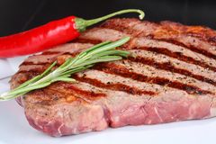 Beef steak with red chili pepper and rosemary Stock Image