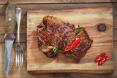 Beef steak with red chillies on wood and table Royalty Free Stock Photos