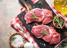 Raw beef steak with herbs top view. Beef steak rib eye on a cutting board with rosemary and spices. Fresh meat uncooked. Top view copy space Stock Photos