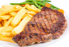 Beef Steak. Ribeye Steak with French Fries and green beans from above over white background royalty free stock photo