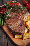 Beef steak with roasted potato. Beef rib-eye steak with roasted potato and vegetables Royalty Free Stock Images