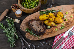 Beef steak with roasted potatoes in rustic kitchen Royalty Free Stock Photography
