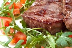 Beef steak with rocket salad. Juicy fried beef steak with rocket salad and sliced tomatoes Royalty Free Stock Photos