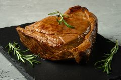 Beef steak with rosemary on a background with open space for text design or restaurant menus. Horizontal photo.  royalty free stock photography