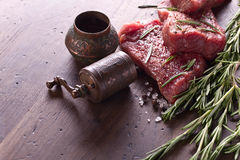 Beef steak with rosemary , salt and pepper. Beef steaks with rosemary , salt and pepper on a old wooden table .Old brass pepper mill Stock Photography