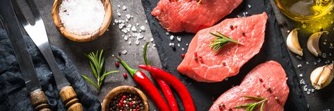 Beef steak with rosemary and spices on black background Stock Photos