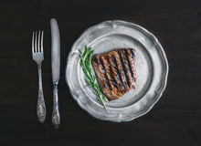 Beef steak with rosemary on a vintage metal plate over a dark wo Royalty Free Stock Photos