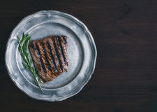 Beef steak with rosemary on a vintage metal plate over a dark wo Stock Image