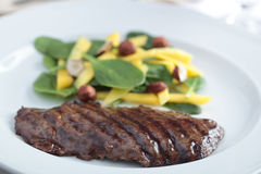 Beef steak with salad. Grilled beef steak with mango, spinach, and nut salad Royalty Free Stock Photos