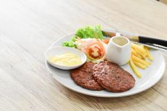 Beef steak, salad and french fries on a vintage wood background royalty free stock image