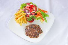 Beef steak with sauteed pepper and onions, french fries and vege Royalty Free Stock Image