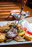 Beef Steak. Sirloin steak. Delicious juicy beef steak on fork. grill  vegetables Royalty Free Stock Photos
