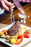 Beef Steak. Sirloin steak. Delicious juicy beef steak on fork. grill  vegetables Royalty Free Stock Photo