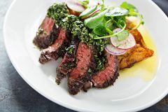 Beef steak sliced on a plate. With green sauce and roasted potatoes Royalty Free Stock Image
