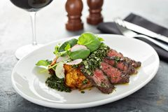 Beef steak sliced on a plate. With green sauce and roasted potatoes Stock Photo