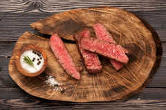 Beef steak slices on a wooden board. Beef steak slices, rosemary and salt and pepper Stock Image