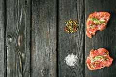 Beef steak and spices. Raw steak on the old board sprinkled with spices Stock Photos
