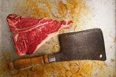 Beef steak t-bone with vintage butcher cleaver knife. On baked tin backdrop royalty free stock photos