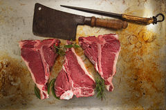 Beef steak t-bone with vintage butcher cleaver knife. On baked tin backdrop royalty free stock photography