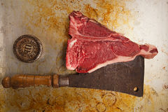 Beef steak t-bone with vintage butcher cleaver knife. 1lb weight on old pan royalty free stock photo
