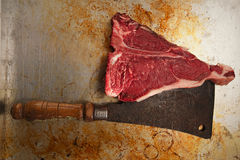 Beef steak t-bone with vintage butcher cleaver knife. On metal backdrop stock photography
