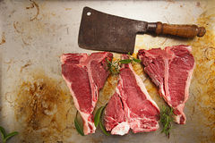 Beef steak t-bone with vintage butcher cleaver knife. On old pan royalty free stock image