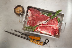 Beef steak t-bone with vintage meat fork. On baked tin backdrop royalty free stock photos