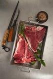 Beef steak t-bone with vintage meat fork. On metal backdrop royalty free stock image