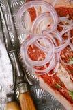 Beef steak t-bone with vintage meat fork on metal backdrop. Beef steak t-bone with vintage meat fork and knife on metal backdrop stock images