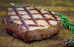 Beef steak with twig rosemary on a wooden table. Royalty Free Stock Photography