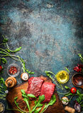 Beef steak and various ingredients for cooking on rustic wooden background, top view, frame. Royalty Free Stock Images
