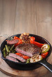 Beef steak with vegetables. Beef steak with vegetables on a cast-iron frying pan. Copy space, selective focus stock image
