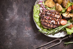 Beef steak with vegetables on plate above. Grilled beef steak with vegetables and rosemary top view on grunge surface with copy space stock photography