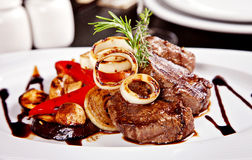 Beef steak with vegetables, rosemary and soy sause. Served on white plate in restaurant stock photo