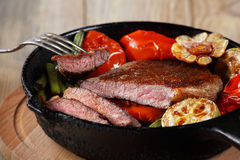 Beef steak with vegetables. Selective focus. Beef steak with vegetables on a cast-iron frying pan close-up. Selective focus royalty free stock image