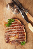 Beef steak with vintage meat fork and knife Stock Photography