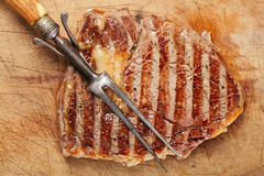 Beef steak with vintage meat fork Stock Photos