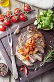 Beef steak well done with tomato and pepper salsa. On a dark wooden background royalty free stock images