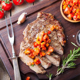 Beef steak well done with tomato and pepper salsa on a wooden background royalty free stock image