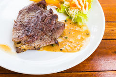 Beef steak on white dish with salad and french fries Stock Photography