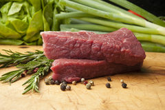 Beef steak on a wooden board, close up. Wooden cutting board with beef, peppercorns and rosemary Stock Photography