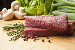 Beef steak on a wooden board, close up. Wooden cutting board with beef steak, peppercorns and rosemary Stock Photos