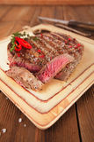 Beef steak on a wooden board and table Stock Image