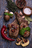 Beef Steak on wooden board. Tasty Beef Steak with garlic and basil on black board, backgrouund stock photo